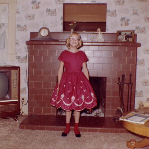 Carol (Satterfield) Bridenstine in front of the fireplace in her Corona home.