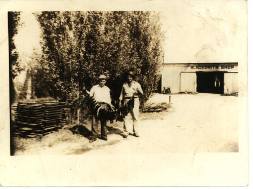 Two men, unknown, holding fish in front of Blacksmith shop.