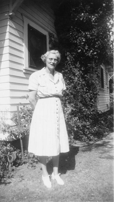"Luellla Bridenstine ""Mamma B"" standing in her yard at 1208 Palm"