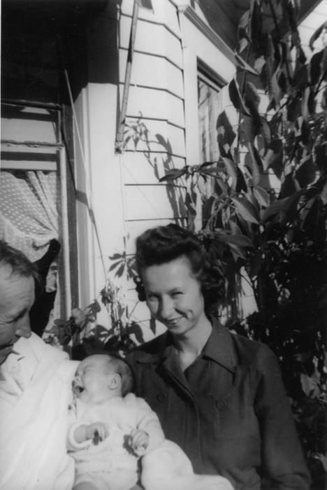 "Don Edgar Bridenstine holding William Edward Pine, Jr. as William's mother Barbara Jean Pine (Bridenstine) looks on. The note on the back of the original photograph was, ""Ah come on smile Billy, 1944 ."" The Bridenstine Family lived at 1208 Palm."
