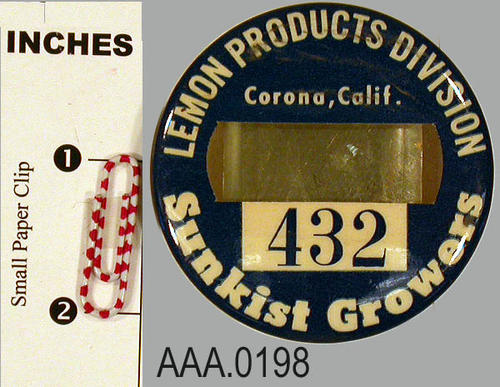 "This artifact is a badge button.  It has a blue background with white lettering.  The  text at the top of the button reads, "" Lemon Products Division, Corona, Calif.,"" Below this text is a  window for the placement of a name.  Under the name window is the number 432 with the text, ""Sunkist Growers,"" below the number. C. 1954."