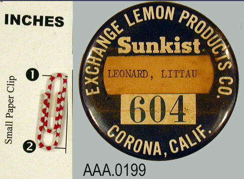 "This artifact is a badge button.  It has a blue background with white lettering.  The text at the top of the button reads, "" Exchange Lemon Products, Sunkist.""  There is a window below for the placement of a name.  The name appearing on this button is, ""Leonard, Littau. Under the name window is the number 604 with the text, ""Corona, Calif."""