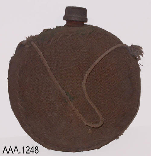 This artifact is a large burlap and metal canteen with a line strap.