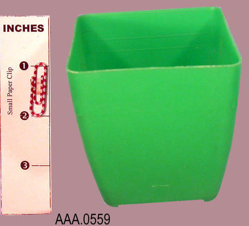 This artifact is a small, green plastic container with four holes in the bottom                 and is used to start young plants.