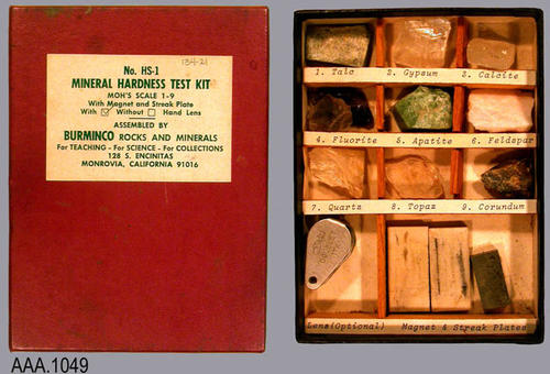 "This artifact is a red box containing No. HS1 Mineral Hardness Test Kit with a hand lens.  It is used for the teaching and for collections. The kit measures 5 3/4"" x 4 1/4""."