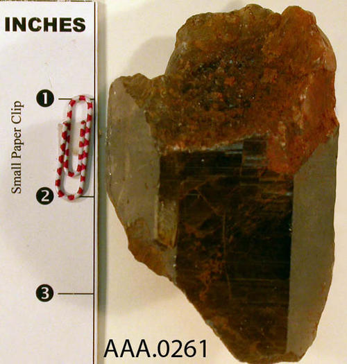This artifact is a large piece of smoky quartz with iron oxide at each end.  It has six sides and is smooth. Donor's Remarks:  This artifact was found near Cajalco and Temescal Road, El Cerrito.