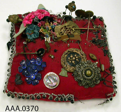This artifact is a cotton jewelry and hat pin pillow.