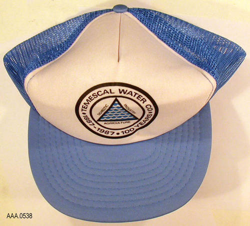 "This artifact is a light blue and white, man's cap.  There is a logo in black letters on a white background.  The blue water symbol is in a triangle with the following text:  ""Temescal Water Co., 1887-1987 - 100 years."""