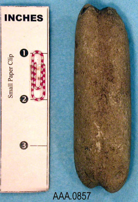 "This artifact is a gray groved sinker stone.  It measures 4"" x 1 1/4"" x 1""."