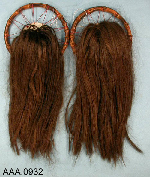 This artifact collection consists of  replicas of human scalps.  The brown hair is sewn onto cheese cloth which in turn is attached to a wooden ring.