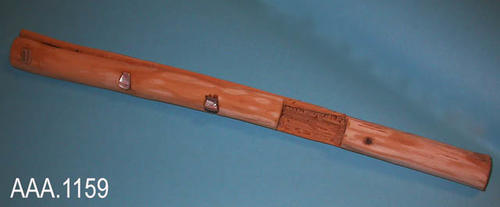 "This artifact is a reproduction of a clapper stick which is a wooden ceremonial flute with three pieces of shell imbedded.  The wood is split to the cutout.  This is a California, Native American  instrument.  It measures 16"" (L) and 1"" in Diameter."