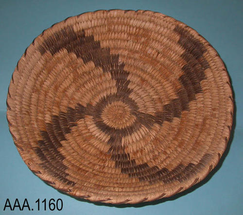 This artifact is a woven, Native American basket that is tan and dark brown in color.