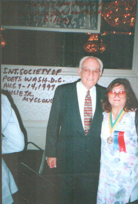 Julie Luna at the annual meeting of the International Society of poets. She is standing next to an unidentified man.