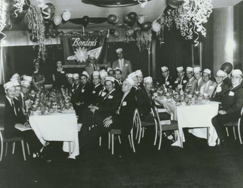 Group of men seated at dinner tables.