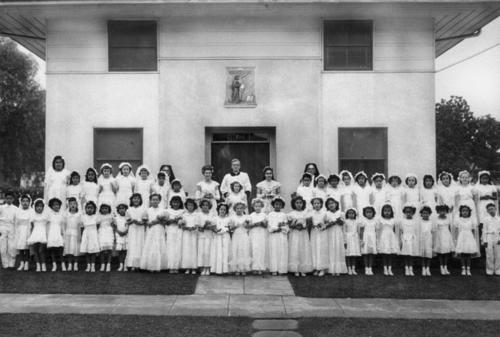 Monsignor Thompson, Sylvia Martinez (Barnett). First communion in front of St. Edwards convent.