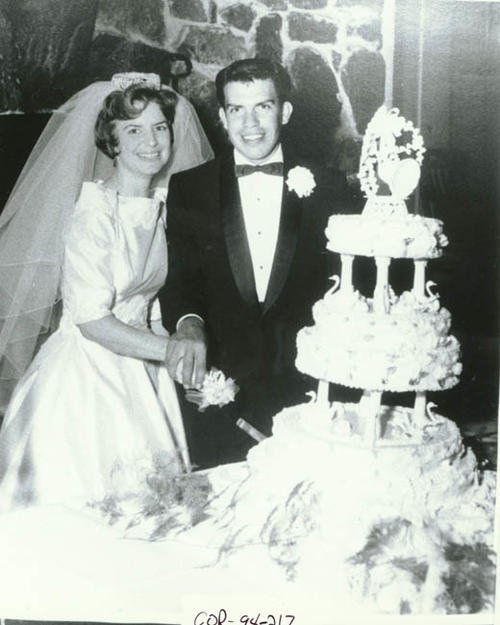 Wedding photo of Dioniscio and Carol (Soost) Salgado.  The couple is pictured cutting the wedding cake.