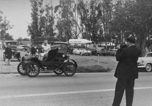 Seventy-fifth (75th) Anniversary of Corona Celebration.  Rudy Ramos is taking a photo of a car as it passes.