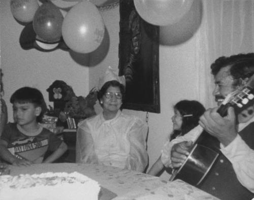Charlotte Balderas Enrique's seventy-some birthday.  Left to right: great grandson, Robert Martinez, Charlotte's granddaughter, Jennifer Enriquez, Tony Ramirez playing the guitar. Party held at the home of Beatrice Ramirez on 844 West Hacienda in Corona.