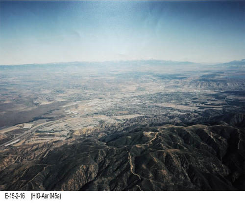 "This is a color aerial view of Corona. The photograph shows what would be seen looking NE from west Corona towards the San Bernardino Mountains. -  MEASUREMENTS:  11"" x 14"" - CONDITION:  This photo is in good condition.  This photograph is kept in a Mylar sleeve. -  COPIES:  1."