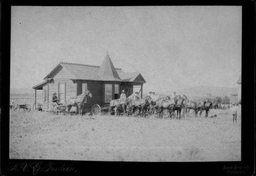 View of photo from Auburndale to Buena Vista and Olive in South Riverside.  This house was built by Leo Kroonen on the banks of the Santa Ana River in Auburndale in 1889.  It was their first home.  It was moved to Corona (then South Riverside) in 1891, to the corner of Buena Vista and Olive Streets where it still stands though it was damaged by fire later on.  The man in the cart is Ed Pine, twin brother of Edward Pine.  He was the one who moved the house from Auburndale to where it now stands.