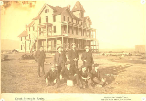 Charles Wall is the last man on the right, sitting down.  Corona's first large hotel, built about 1888 by A.S. Garretson. Cost about $15,000. R.B. Taylor, the leader on the founding of the colony, stands apart on the left.  The hotel operated for many years by O.A. Smith, and burned down in 1899.