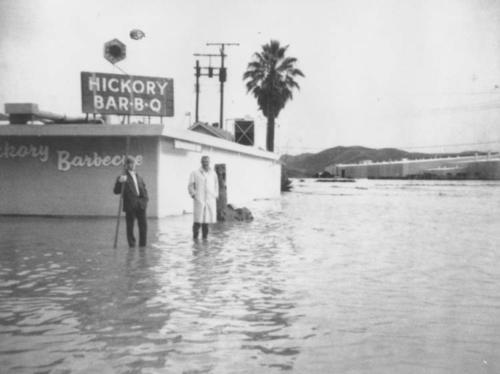 Flood waters in Corona near Home Gardens. The Hickory Bar-B-Q is surrounded by water. Bob Davis and Ken Dickerson are pictured in front of the restaurant.