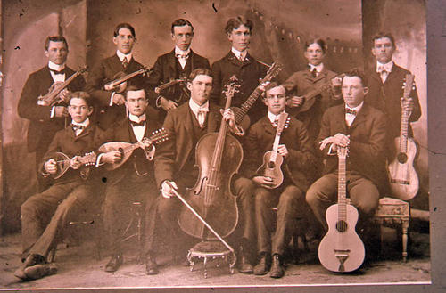 This slide is a photograph of an eleven member, male, string orchestra. - SLIDE CONDITION:  Deteriorating.  The image is clear, but would need retouching to remove spots for publication use. KEY WORDS:  violin, guitar, cello, mandolin, music