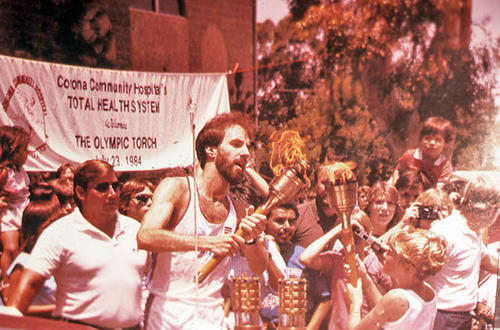 This slide is of the Olympic Torch being carried in Corona on 07/23/1984.  The banner for the Corona Community Hospital is in the background.  SLIDE CONDITION:  Good