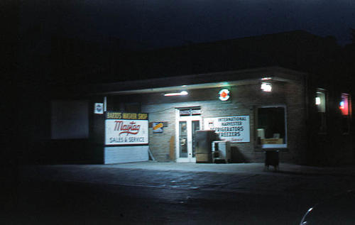 This slide is a photograph of Barto's Washer Shop taken at night 08/1951. - SLIDE CONDITION:  Good