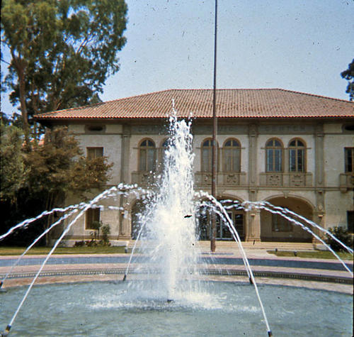 This slide is of the Corona Civic Center, formerly the Corona Senior High School, and was used as the City Hall until 2007 when a new facility opened behind the old structure. This view shows the front of the complex looking north from the south side of the fountain. - SLIDE CONDITION:  Good