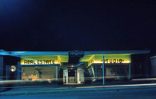 This slide is of the Arcade Building in Corona at night.  The building at the time the photograph was taken had a real estate office and studio and tenants. SLIDE CONDITION:  Good
