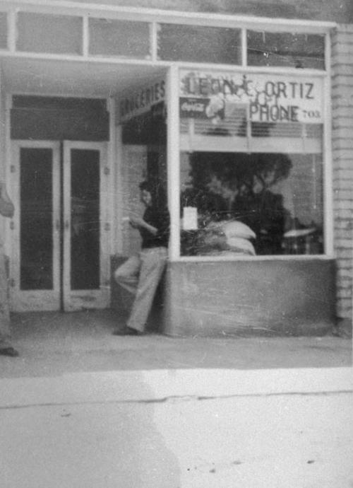 Ramona Ortiz standing in doorway of Leon C. Ortiz and Sons Tortilla Store on North Main Street between 2nd and 3rd Streets.