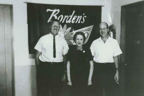 Picture of three people in front of a Borden's Dairy building.