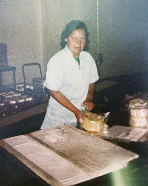 Woman working at the Ortiz Tortilla Store. Don Leon Tortilla Store at 107 West Third Street.  Picture of the store after it was enlarged to accommodate a four-line tortilla machine; silo holds corn that would be ground for masa.