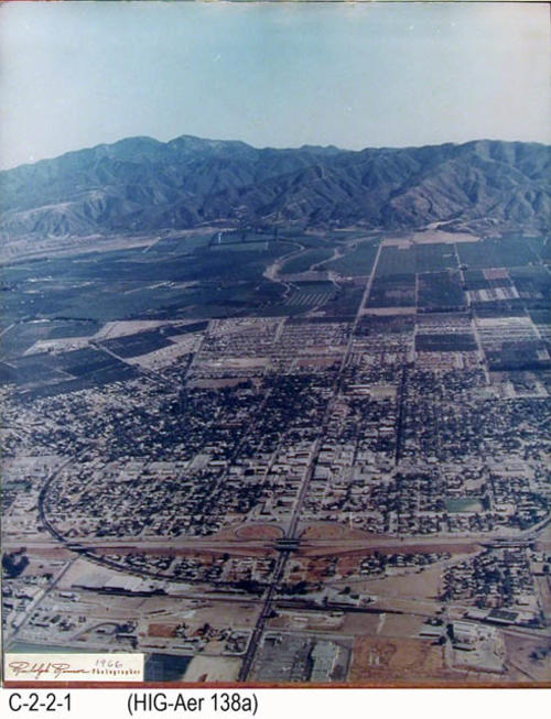 "This is an aerial view of Corona looking south.  A notation in the lower left corner says Rudolph Ramos, Photographer - 1966.  MEASUREMENTS:  25"" X 20"" - CONDITION:  This photo is in good condition with the exception that the color in the photograph is deteriorating.  The photo has a strong blue cast. - COPIES:  1."