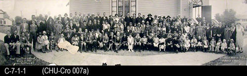 "This photograph is a picture of the Bible School at the First Christian Church of Corona.  Students are in front of the church. The church was located at 9th and Main St.  MEASUREMENTS:  8"" X 28"" - CONDITION:  There is a 1 1/2"" x 2 1/2"" piece missing  about 7"" from the left end.  There are several major cracks in the picture:  1 near the left end and 2 near the right end.  The bottom edge is damaged. - COPIES:  1 - DIGITAL RESTORATION:  The library has a digitally restored copy of this photograph."