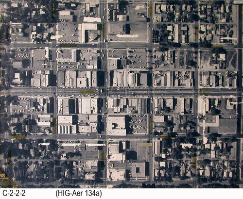 "This aerial photograph shows a small area in the center of Corona.  E-W streets are 3rd to 8th, and N-S streets are Victoria, Main and Washburn.  Written in the corner is the name:  M. G. Robinson.  There is a Mylar overlay that has some of the business locations that have been written on the protective covering.  MEASUREMENTS:  30.5"" X 40.5"" - CONDITION:  This aerial photograph has numerous, irregular white areas where tape has been pulled off.  - COPIES 1. - PICTURE ORIENTATION:  Top is NORTH. (Main intersecting streets are:  Main St. and 6th St.)"