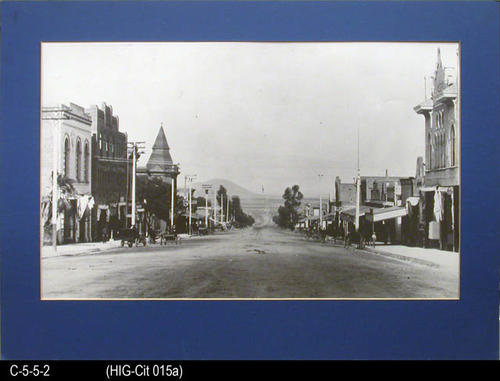"This photo is an enlarged copy of the original of Main street Corona and shows the Libery Stables, Glass and Sons Hardware, Railroad, and the Odd Fellows Hall.  MEASUREMENTS:  Photo is 16"" x 20"" - Matted:  17"" x 23 1/2"" - CONDITION:  The Mat and photo are in very good condition. - COPIES:  1."