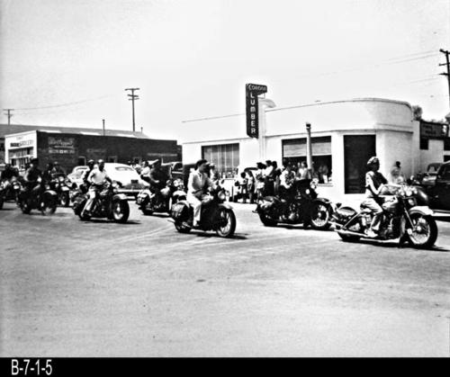 "This is a B/W photograph shows members of a motorcycle club in front of Corona Lumber Co. located at 402 Main Street, Corona, CA. MEASUREMENTS: 16"" x 20"" - CONDITION:  Very good.  This photograph is kept in a Mylar sleeve.  -  COPIES:  1"