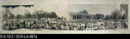 "This photograph is a picture of Lincoln Elementary pupils and teachers taken c.1921.  They are posing on the left side of the school building next to trees and near the street.  MEASUREMENTS:  8"" X 34"" - CONDITION:  This photograph is in a protectice sleeve.  The bottom border has four small creases that are about 1"" in length.  COPIES:  This is copy 1."