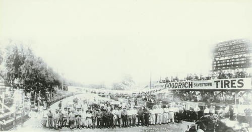 Photo of the line-up of drivers and mechanics at the starting line for the 1916 car race.