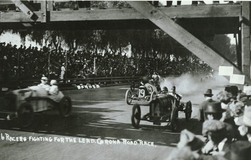 "Photo of a race at Corona Grand Boulevard.  The notation on the photo reads ""Six races Fighting for The Lead."" ""Corona Road Race.""  Two race cars are numbered #19 and #14, others are not known."