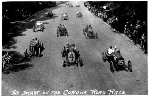 Race cars at the start of the corona road races with spectators at the side.