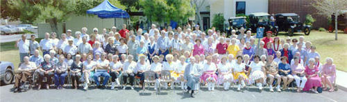 Group photo of people on the south lawn of the senior citizen's center.