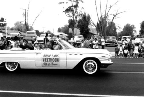 Dutch and Mrs. Velthoen riding in a car as part of a parade.  Dutch Velthoen was the Mayor.