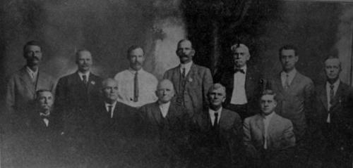 Studio portrait of the Corona City Officers (City Council). Top Row: A.B. Tuthill, Street Supt., M. Terpening, Clerk,  J.L. Merriam, Treasurer. G.C. Alexander, Marshall, Cuthbert Guylly, Engineer, G.R. Freeman, Attorney, O.P. Hall, Recorder. Trustees, seated: F.J Mueller, Edward Davis, H.H. Holmes, Mayor, E.A. Stobbs, A.H. Cross, Dr. W.S. Davis, Health Officer, W.J. Pentelow, Tree Warden, B.E. Savery, Building Inspector.