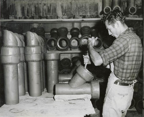 Man working on a clay pipe.