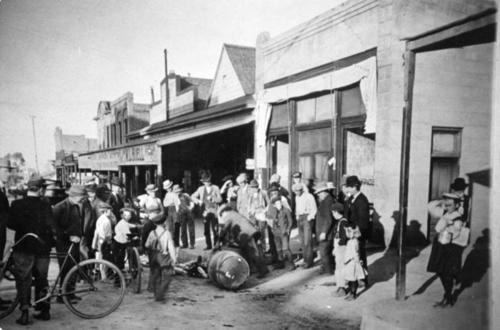 Deputy Marshall destroying illegal whiskey in front of Corona's first Post Office on Main Street. A crowd of people, women and children included, gathered to witness the event.