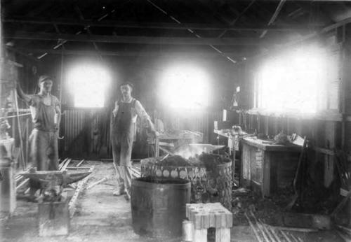 Two men standing in a blacksmith shop.