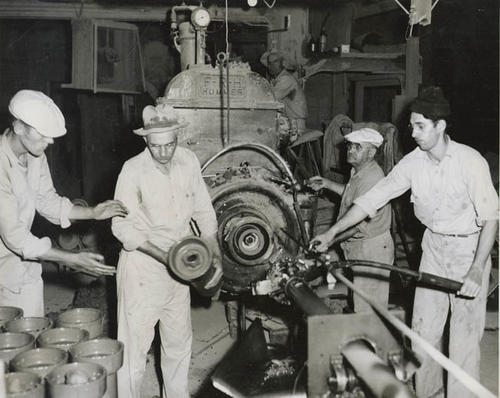 Four men working with a clay pipe machine